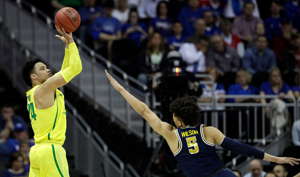 . Oregon forward Dillon Brooks, left, shoots over Michigan forward D.J. Wilson during the first half of a regional semifinal of the NCAA men\'s college basketball tournament, Thursday, March 23, 2017, in Kansas City, Mo. (AP Photo/Charlie Riedel)