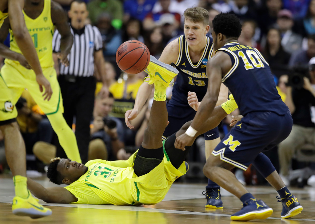 . Oregon guard Dylan Ennis, left, fights for a loose ball with Michigan\'s Derrick Walton Jr. (10) and Moritz Wagner (13) during the first half of a regional semifinal of the NCAA men\'s college basketball tournament, Thursday, March 23, 2017, in Kansas City, Mo. (AP Photo/Charlie Riedel)