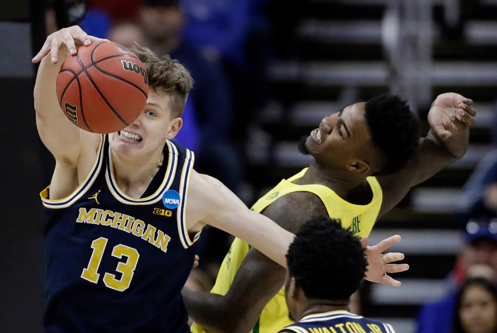 . Michigan forward Moritz Wagner (13) fights for a rebound with Oregon forward Jordan Bell during the first half of a regional semifinal of the NCAA men\'s college basketball tournament, Thursday, March 23, 2017, in Kansas City, Mo. (AP Photo/Charlie Riedel)