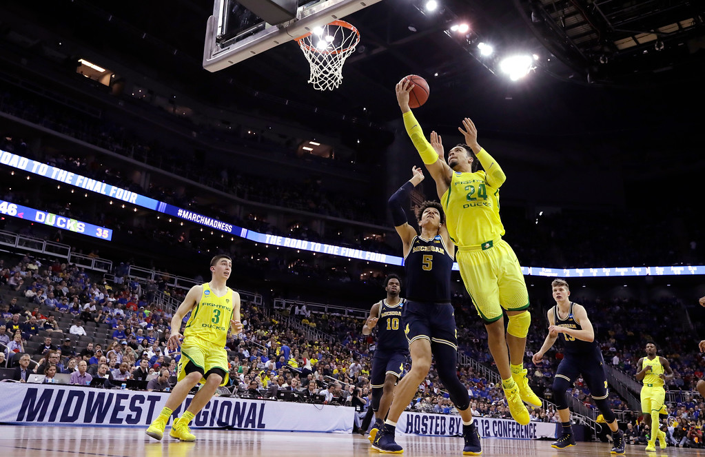 . Oregon forward Dillon Brooks (24) drives to the basket past Michigan forward D.J. Wilson (5) during the second half of a regional semifinal of the NCAA men\'s college basketball tournament, Thursday, March 23, 2017, in Kansas City, Mo. (AP Photo/Charlie Riedel)