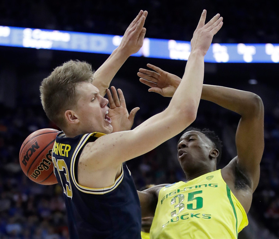 . Michigan forward Moritz Wagner, left, and Oregon forward Kavell Bigby-Williams (35) compete for the ball during the second half of a regional semifinal of the NCAA men\'s college basketball tournament, Thursday, March 23, 2017, in Kansas City, Mo. (AP Photo/Charlie Riedel)