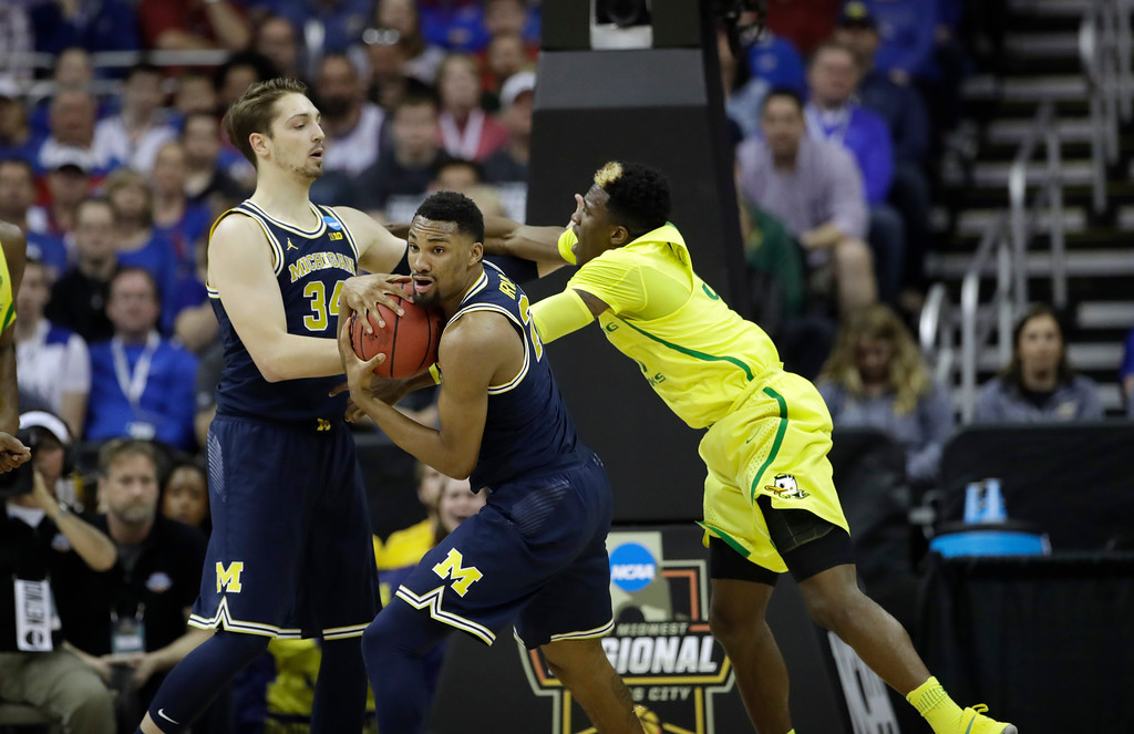 . Michigan guard Zak Irvin, center, grabs a rebound in front of teammate Mark Donnal, left, and Oregon guard Dylan Ennis, right, during the first half of a regional semifinal of the NCAA men\'s college basketball tournament, Thursday, March 23, 2017, in Kansas City, Mo. (AP Photo/Charlie Riedel)