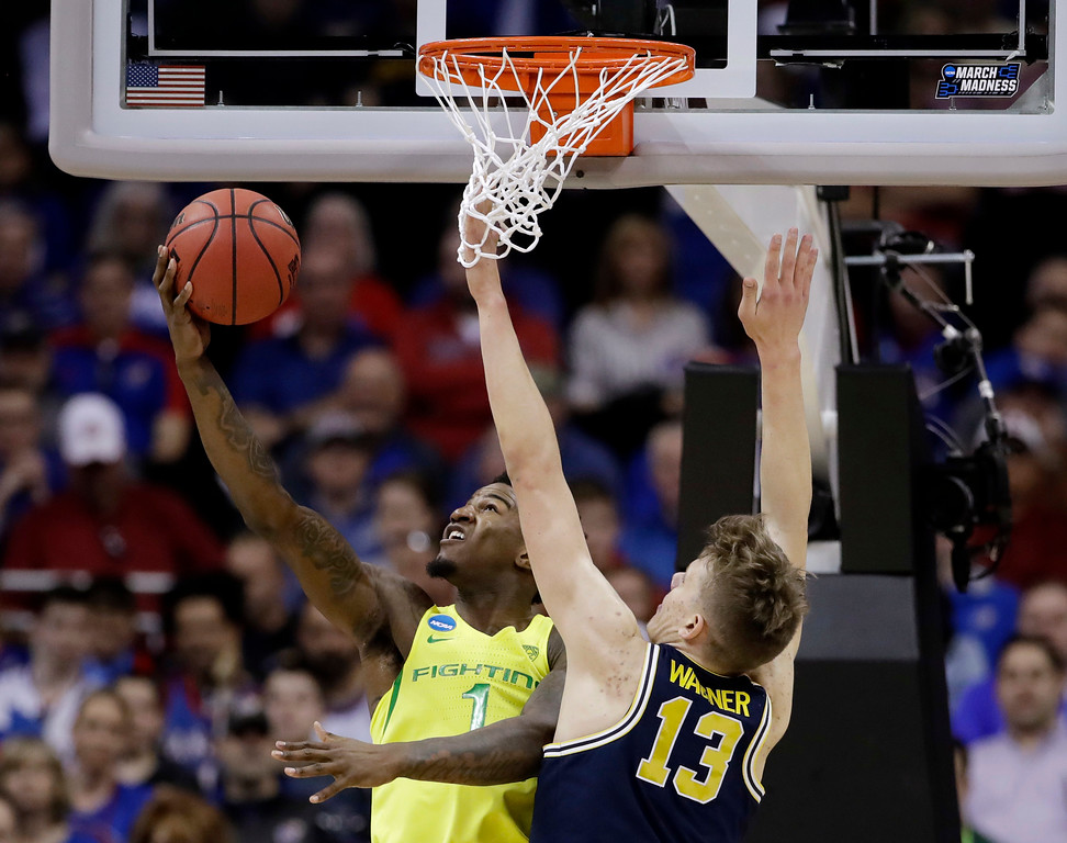 . Oregon forward Jordan Bell, left, drives to the basket in front of Michigan forward Moritz Wagner during the first half of a regional semifinal of the NCAA men\'s college basketball tournament, Thursday, March 23, 2017, in Kansas City, Mo. (AP Photo/Charlie Riedel)