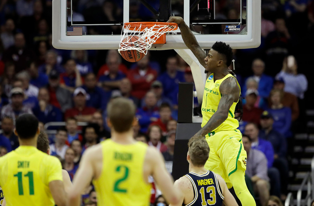 . Oregon forward Jordan Bell dunks the ball over Michigan forward Moritz Wagner (13) during the first half of a regional semifinal of the NCAA men\'s college basketball tournament, Thursday, March 23, 2017, in Kansas City, Mo. (AP Photo/Charlie Riedel)