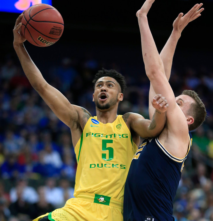 . Oregon guard Tyler Dorsey (5) drives to the basket past Michigan guard Duncan Robinson during the first half of a regional semifinal of the NCAA men\'s college basketball tournament, Thursday, March 23, 2017, in Kansas City, Mo. (AP Photo/Orlin Wagner)