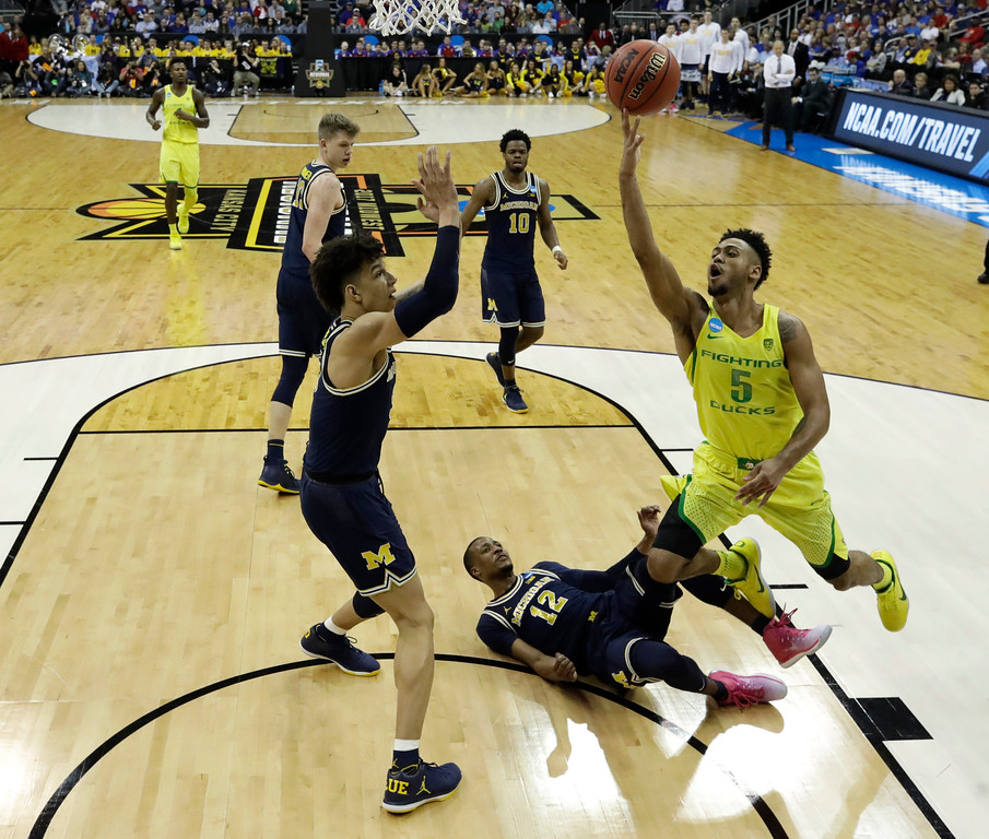 . Oregon guard Tyler Dorsey (5) drives to the basket over Michigan\'s D.J. Wilson, left, and Muhammad-Ali Abdur-Rahkman (12) during the second half of a regional semifinal of the NCAA men\'s college basketball tournament, Thursday, March 23, 2017, in Kansas City, Mo. (AP Photo/Charlie Riedel)
