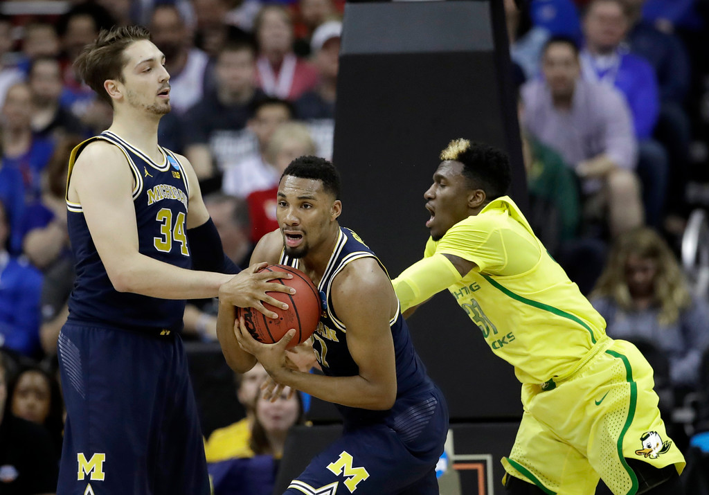 . Michigan guard Zak Irvin, center, grabs a rebound in front of teammate Mark Donnal, left, and Oregon guard Dylan Ennis during the first half of a regional semifinal of the NCAA men\'s college basketball tournament, Thursday, March 23, 2017, in Kansas City, Mo. (AP Photo/Charlie Riedel)
