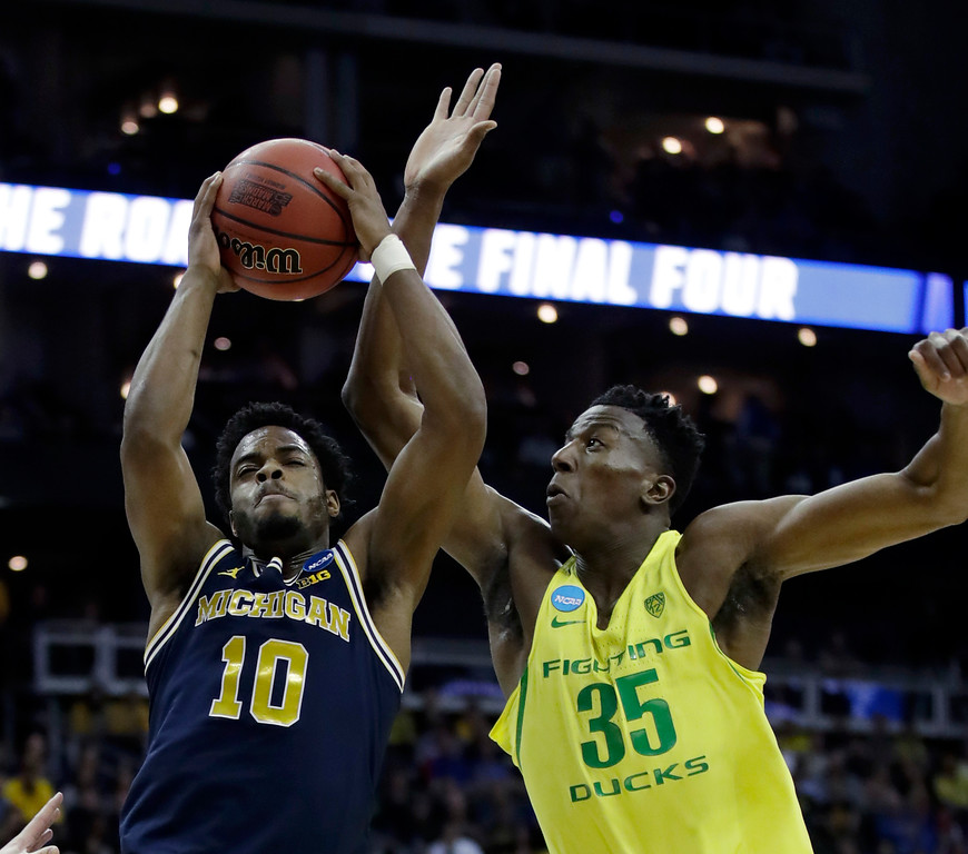 . Michigan guard Derrick Walton Jr. (10) grabs a rebound next to Oregon forward Kavell Bigby-Williams during the first half of a regional semifinal of the NCAA men\'s college basketball tournament, Thursday, March 23, 2017, in Kansas City, Mo. (AP Photo/Charlie Riedel)