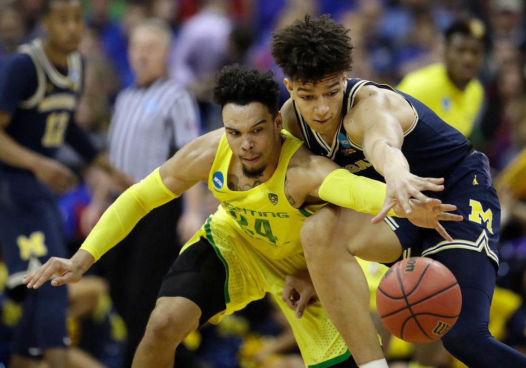 . Oregon forward Dillon Brooks (24) tries to steal the ball from Michigan forward D.J. Wilson, right, during the second half of a regional semifinal of the NCAA men\'s college basketball tournament, Thursday, March 23, 2017, in Kansas City, Mo. (AP Photo/Charlie Riedel)