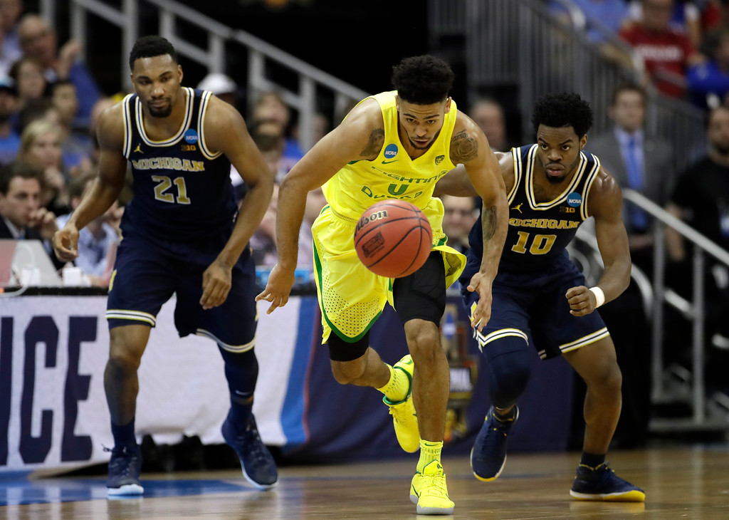 . Oregon guard Tyler Dorsey, center, drives up court ahead of Michigan\'s Zak Irvin, left, and Derrick Walton Jr. during the second half of a regional semifinal of the NCAA men\'s college basketball tournament, Thursday, March 23, 2017, in Kansas City, Mo. (AP Photo/Charlie Riedel)