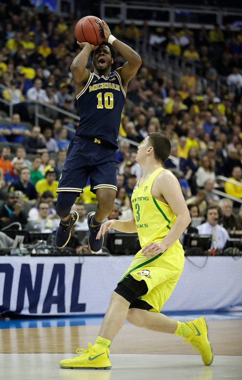 . Michigan guard Derrick Walton Jr. (10) shoots over Oregon guard Payton Pritchard during the first half of a regional semifinal of the NCAA men\'s college basketball tournament, Thursday, March 23, 2017, in Kansas City, Mo. (AP Photo/Charlie Riedel)