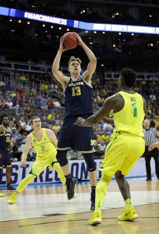 . Michigan forward Moritz Wagner (13) shoots over Oregon forward Jordan Bell, right, during the first half of a regional semifinal of the NCAA men\'s college basketball tournament, Thursday, March 23, 2017, in Kansas City, Mo. (AP Photo/Charlie Riedel)