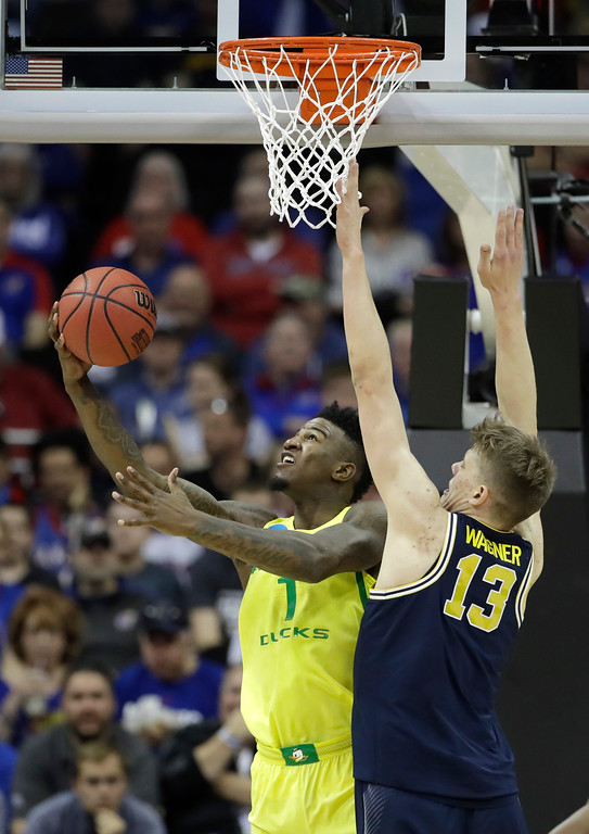 . Oregon forward Jordan Bell drives to the basket in front of Michigan forward Moritz Wagner (13) during the first half of a regional semifinal of the NCAA men\'s college basketball tournament, Thursday, March 23, 2017, in Kansas City, Mo. (AP Photo/Charlie Riedel)
