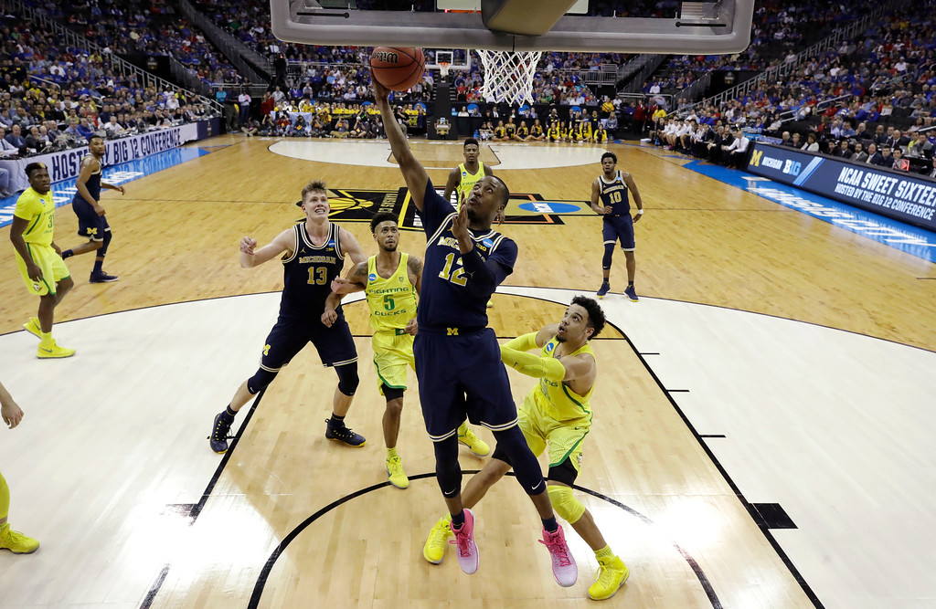 . Michigan guard Muhammad-Ali Abdur-Rahkman (12) drives to the basket over Oregon forward Dillon Brooks, right, during the first half of a regional semifinal of the NCAA men\'s college basketball tournament, Thursday, March 23, 2017, in Kansas City, Mo. (AP Photo/Charlie Riedel)