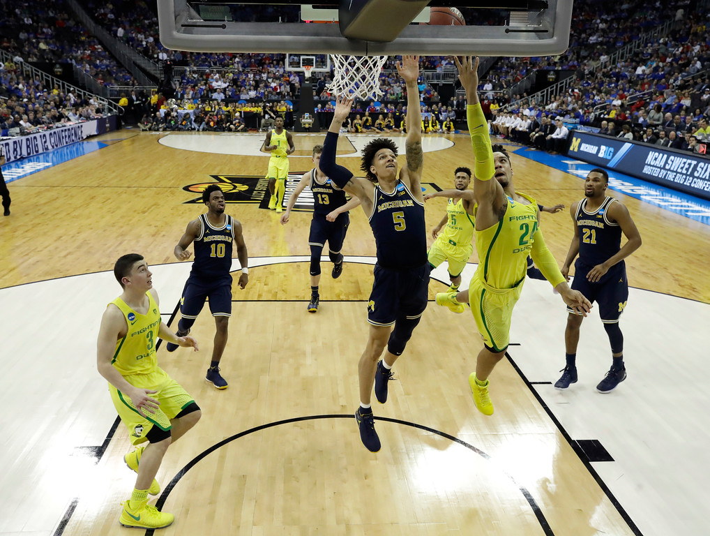 . Oregon forward Dillon Brooks drives to the basket ahead of Michigan forward D.J. Wilson (5) during the second half of a regional semifinal of the NCAA men\'s college basketball tournament, Thursday, March 23, 2017, in Kansas City, Mo. (AP Photo/Charlie Riedel)
