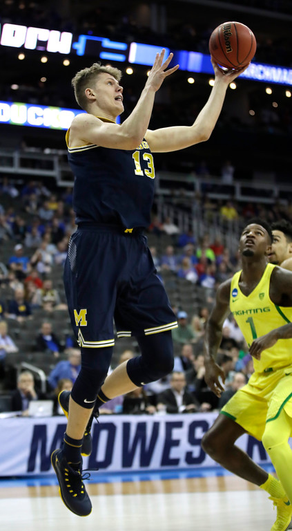 . Michigan forward Moritz Wagner (13) drives to the basket over Oregon forward Jordan Bell (1) during the first half of a regional semifinal of the NCAA men\'s college basketball tournament, Thursday, March 23, 2017, in Kansas City, Mo. (AP Photo/Charlie Riedel)