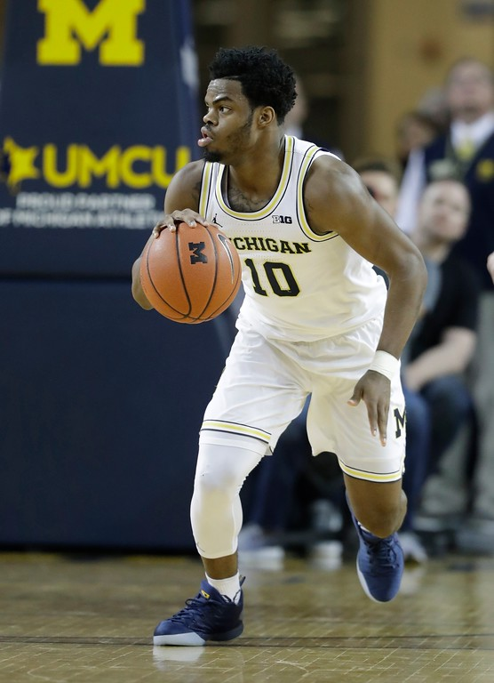 . Michigan guard Derrick Walton Jr. brings the ball up court during the second half of an NCAA college basketball game against Wisconsin, Thursday, Feb. 16, 2017, in Ann Arbor, Mich. (AP Photo/Carlos Osorio)