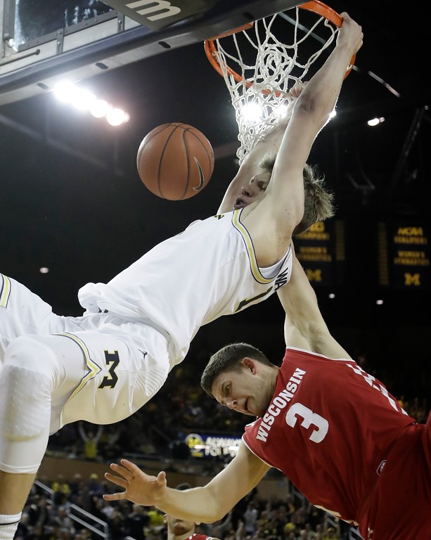. Michigan forward Moritz Wagner makes a dunk defended by Wisconsin guard Zak Showalter (3) during the second half of an NCAA college basketball game, Thursday, Feb. 16, 2017, in Ann Arbor, Mich. Wagner had 21 points in the win over Wisconsin 64-58. (AP Photo/Carlos Osorio)