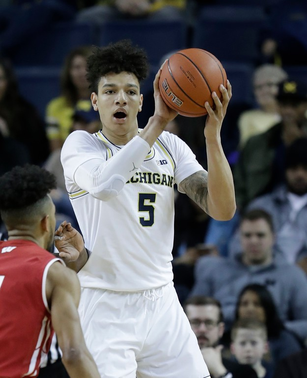 . Michigan forward D.J. Wilson passes the ball during the first half of an NCAA college basketball game against Wisconsin, Thursday, Feb. 16, 2017, in Ann Arbor, Mich. (AP Photo/Carlos Osorio)