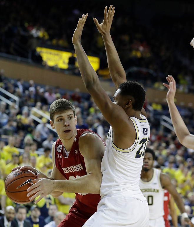 . Wisconsin forward Ethan Happ looks to pass around Michigan guard Zak Irvin (21) during the first half of an NCAA college basketball game, Thursday, Feb. 16, 2017, in Ann Arbor, Mich. (AP Photo/Carlos Osorio)