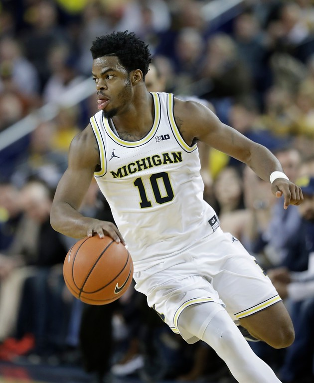 . Michigan guard Derrick Walton Jr. dribbles during the second half of an NCAA college basketball game against Wisconsin, Thursday, Feb. 16, 2017, in Ann Arbor, Mich. (AP Photo/Carlos Osorio)