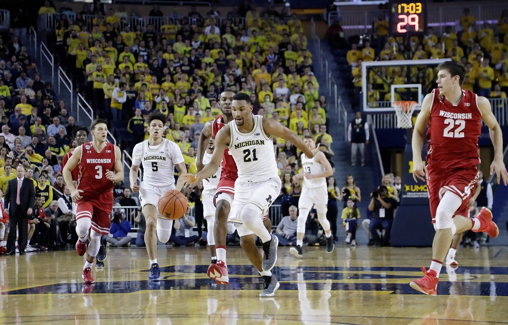 . Michigan guard Zak Irvin (21) brings the ball up court during the second half of an NCAA college basketball game against Wisconsin, Thursday, Feb. 16, 2017, in Ann Arbor, Mich. (AP Photo/Carlos Osorio)