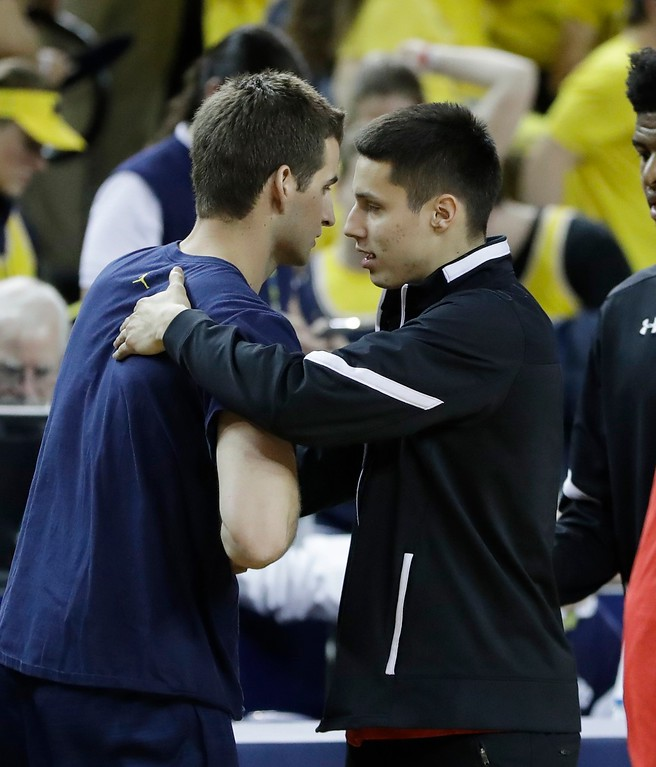 . Wisconsin guard Bronson Koenig, right, meets Michigan guard Andrew Dakich after an NCAA college basketball game, Thursday, Feb. 16, 2017, in Ann Arbor, Mich. (AP Photo/Carlos Osorio)