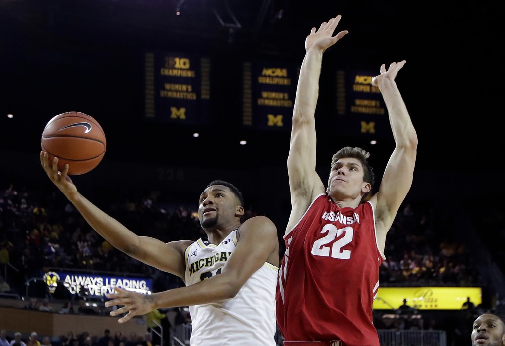 . Wisconsin forward Ethan Happ (22) defends as Michigan guard Zak Irvin makes a layup during the second half of an NCAA college basketball game, Thursday, Feb. 16, 2017, in Ann Arbor, Mich. (AP Photo/Carlos Osorio)