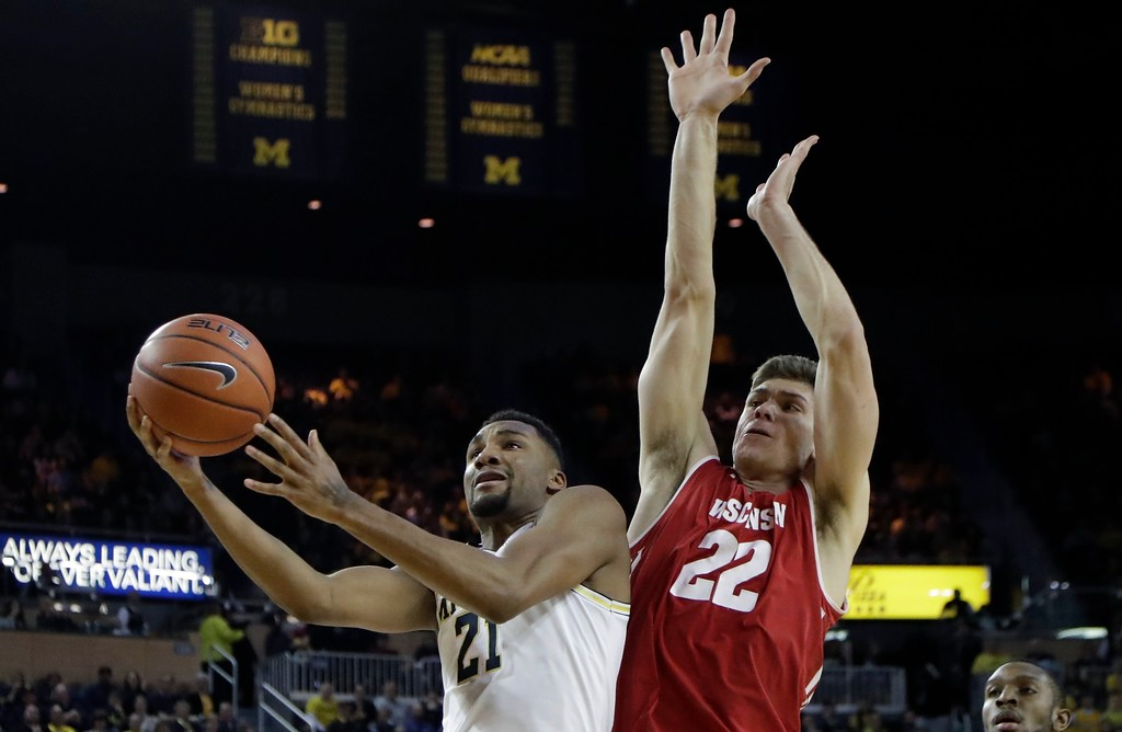 . Michigan guard Zak Irvin (21) shoots while defended by Wisconsin forward Ethan Happ (22) during the second half of an NCAA college basketball game, Thursday, Feb. 16, 2017, in Ann Arbor, Mich. (AP Photo/Carlos Osorio)