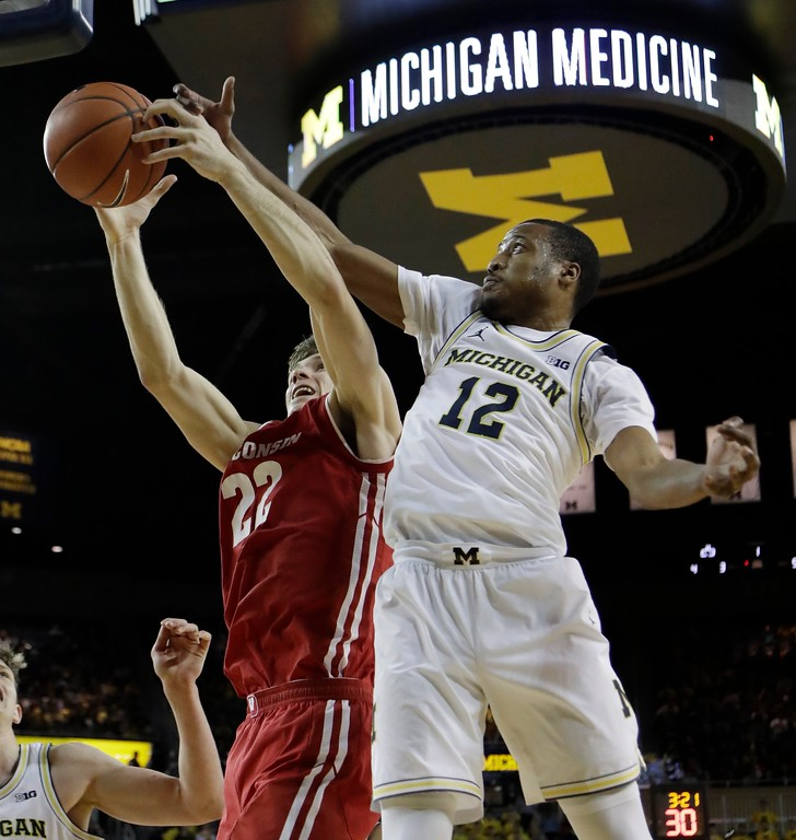 . Wisconsin forward Ethan Happ and Michigan guard Muhammad-Ali Abdur-Rahkman (12) battle for the rebound during the first half of an NCAA college basketball game, Thursday, Feb. 16, 2017, in Ann Arbor, Mich. (AP Photo/Carlos Osorio)
