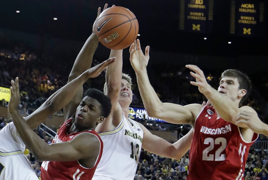 . Michigan forward Moritz Wagner (13) knocks the ball away from Wisconsin guard Khalil Iverson, left, during the second half of an NCAA college basketball game, Thursday, Feb. 16, 2017, in Ann Arbor, Mich. (AP Photo/Carlos Osorio)