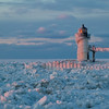 Sunset light warms the frozen channel and pierhead light at St. Joseph, MI<br /> <br /> MI-090125-0171