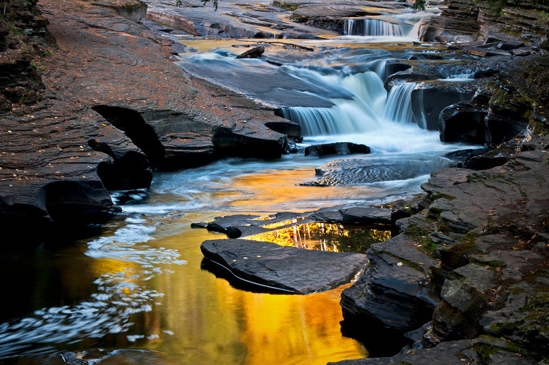 M 131                          The colors of autumn are reflected in a calm pool on the Presque Isle River, Porcupine Mountains Wilderness State Park, Michigan.