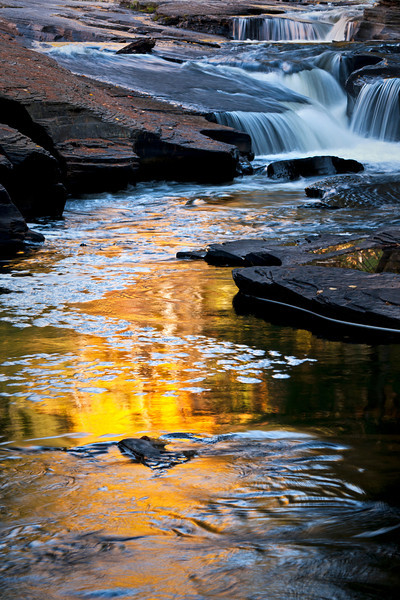M 136                          The colors of autumn are reflected in a calm pool on the Presque Isle River, Porcupine Mountains Wilderness State Park, Michigan.