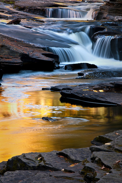 M 127                         The colors of autumn are reflected in a calm pool on the Presque Isle River, Porcupine Mountains Wilderness State Park, Michigan.