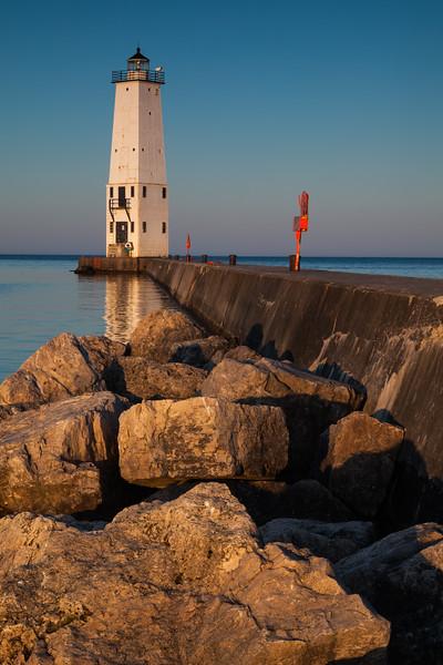 Warm light shines on the Ludington light and pier. Ludington, MI<br /> <br /> MI-090626-0017