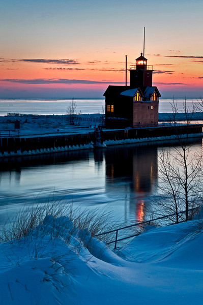 MI 215                        The Holland Harbor South Pierhead Lighthouse, also known as Big Red, stands guard on the icy shore of Lake Michigan at twilight.