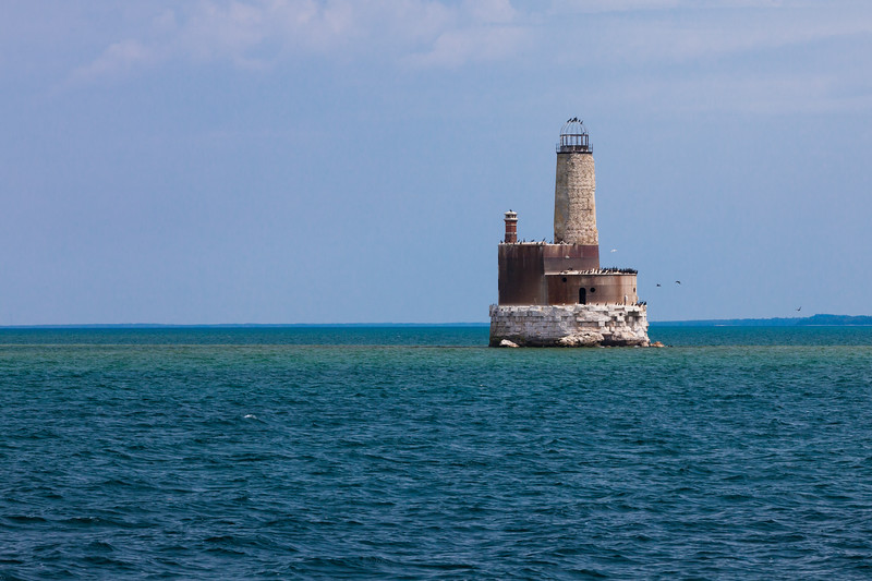 Waugoshance Shoal Light was constructed in 1851 to mark the shoals extending from Waugoshance  Point. It was built of brick and in 1883, sheathed with 3/8-inch thick steel. The light was decommisioned in 1912 and in the early 1940s  became a target for practice bombing. Today it stands without some of the metal casing deteriorating and serving as a bird colony. There are efforts underway to stabilize and possibly restore the light. Straits of Mackinac, MI<br /> <br /> MI-110707-0316