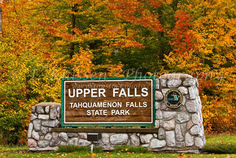 The Upper Tahquamenon Falls sign with fall foliage color near Newberry, Michigan, USA.