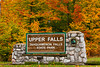The Upper Tahquamenon Falls sign with fall foliage color near Newberry, Michigan, USA.