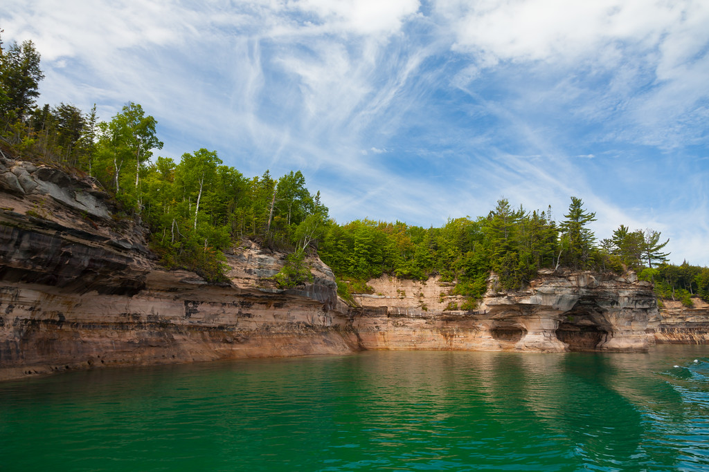 The red cliffs of Pictured Rocks National Lakeshore stand out against the green waters of Lake Superior and the blue sky above. PIctured Rocks National Lakeshore, MI<br /> <br /> MI-090622-0070