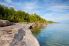 Sometimes traveling the less traveled roads can be very rewarding. After driving a long, narrow and winding dirt road leading to a handful of primitive campsites, I found this shoreline. Lake Superior has a reputation for its tubulent waters but this morning it was very peaceful. Christmas, MI<br /> <br /> MI-090622-0006
