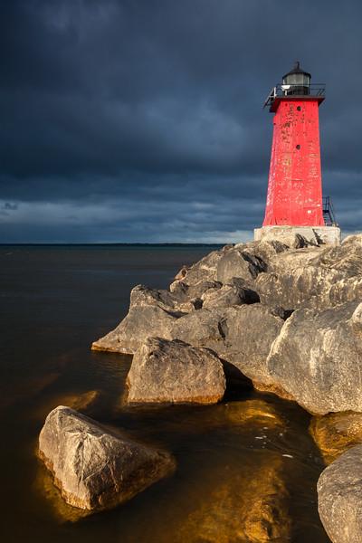 Sunshines illuminates the Manistique East Breakwater Light on a stormy morning. Manistique, MI<br /> <br /> MI-110930-0116