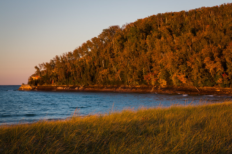 Golden light shines on the grasses and trees on Miners Beach. Picture Rocks National Lakeshore, MI<br /> <br /> MI-120929-0213