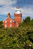 A rose bush blooms next to the Big Bay Lighthouse. Big Bay, MI<br /> <br /> MI-110704-0098