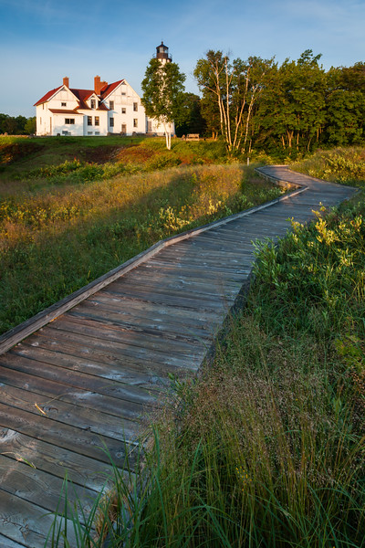 Morning light shines on the Point Iroquois Lihgthouse and boardwalk. Bay Mills, MI<br /> <br /> MI-110707-0014