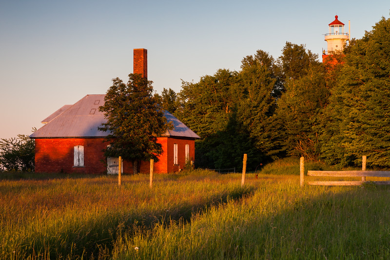 Sunset light shines over fog signal building at the Big Bay Lighthouse grounds. Big Bay, MI<br /> <br /> MI-110703-0048