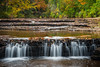 On the way to Munising, I drove over the Riffle River. Through an opening on the brush and shrubs, Autumn color could be seen upstream. Although not a lot of water was flowing, this small waterfall frames nicely the Autumn scene. Upper Peninsula, MI<br /> <br /> MI-080925-0057