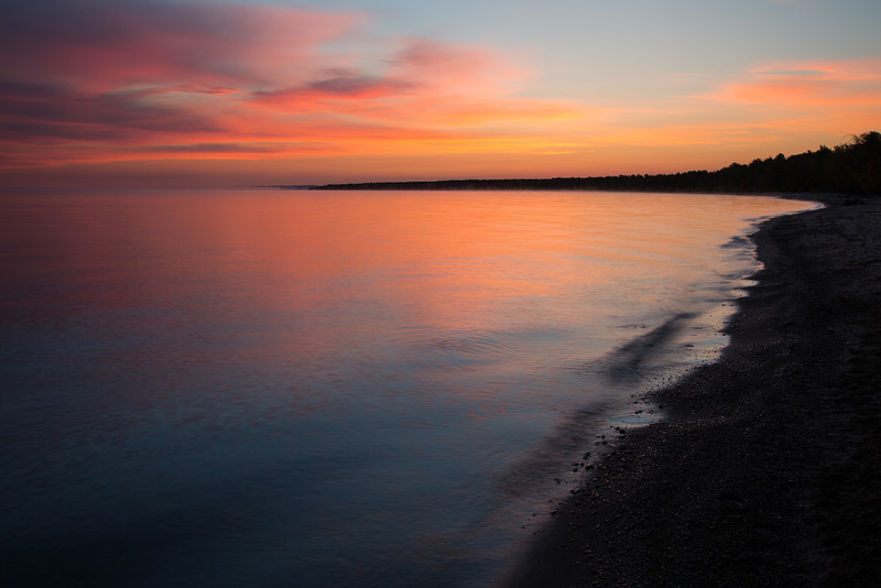 The sky glows with orange hues on a crisp fall morning along the shores of Lake Superior. Silver City, MI<br /> <br /> MI-120928-0008