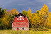 A red barn with fall foliage color in rural Michigan, Upper Peninsula, USA.